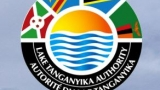 Lake Tanganyika Authority Logo. Flags of the countries bordering the lake in the top half of a circle with the bottom half the words Lake Tanganyika Authority in English and French. In the center of the circle is line art of a lake and sun.